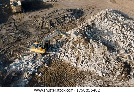 Recycling concrete and construction waste from demolition. Excavator at landfill of the disposa. Reuse of building rubble. Backhoe dig gravel at mining quarry on blue sky background. Out of focus Royalty-Free Stock Photo #1950856402