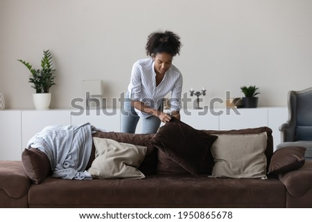 Young African American woman clean cozy new modern apartment or house on weekend day. Millennial biracial female renter or tenant decorate design comfortable couch in living room at home. Royalty-Free Stock Photo #1950865678