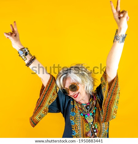 Funny portrait of mature woman. Beautiful lady have fun dressed with seventies costume. Mature woman on colored backgrounds Royalty-Free Stock Photo #1950883441