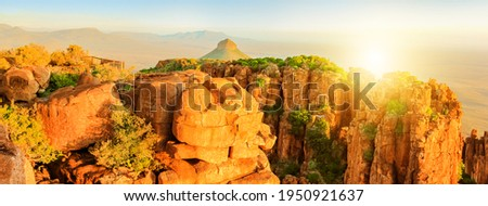 Panorama of Valley of Desolation and observation platform in Camdeboo National Park, Karoo, Eastern Cape near Graaff-Reinet, South Africa at sunset light in afternoon. Banner background. Copy space. Royalty-Free Stock Photo #1950921637