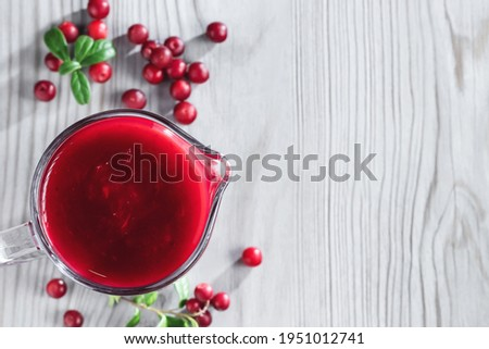 Homemade fresh wild lingonberry sauce in a glass gravy boat, top view, flat lay, copyspace