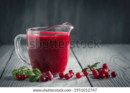 Homemade fresh wild lingonberry sauce in a glass gravy boat, copy space