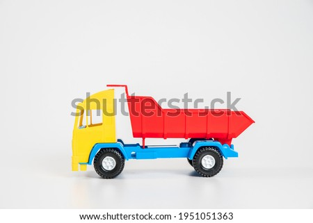 Children's toy plastic car isolated on white background. Multicolored truck.
