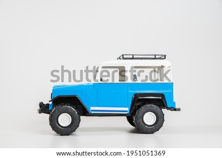 Children's toy plastic car isolated on white background. Blue and white SUV.