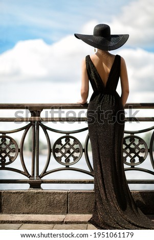 Woman Back Side View in Hat and Evening Dress Outdoor. Fashion Model Rear View looking away. Luxury Lady in long Gown at Promenade looking at Sky Royalty-Free Stock Photo #1951061179