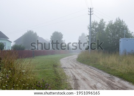 View of a deserted village street. Morning fog. Summer rural foggy landscape. Dirt road, fences and wooden houses. Everyday life in the countryside. Royalty-Free Stock Photo #1951096165