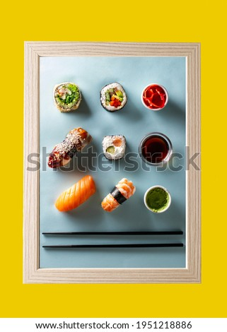 Sushi and rolls, soy sauce and wasabi on a blue background in a light frame on a yellow wall