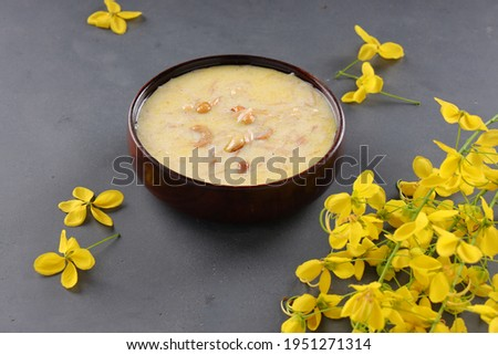 Vermecelli Payasam or Kheer ,South Indian main sweet dish made using vermicelli ,milk,sugar and dry nuts  and beautifully arranged with golden shower flower in the grey background, selective focus.