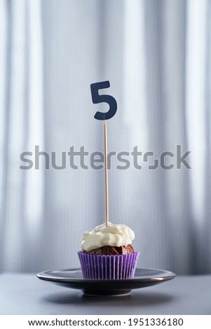 Minimalistic birthday or anniversary digital invitation card concept. Homemade chocolate birthday cupcake with creamy topping and number 5 five on black plate and bright background. Vertical image