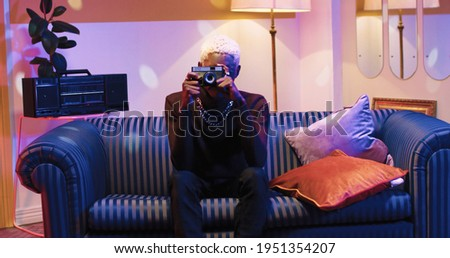 Joyful young handsome African American male with blonde hair taking photos on photo camera while sitting on couch looking at camera and smiling. Vintage happy man taking pictures at home