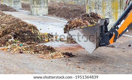Industrial compost plant. Earth mover working with pile of compost in industrial facility. Turning organic waste to compost soil. Royalty-Free Stock Photo #1951364839