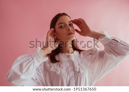 Young beautiful fashionable brunette girl wearing stylish white vintage cotton shirt with lace collar, posing on pink background