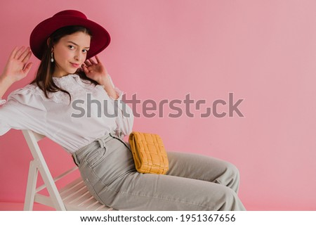 Fashionable woman wearing stylish white vintage cotton shirt with lace collar, marsala color hat, jeans, with small yellow padded leather bag, posing on pink background. Copy, empty space for text