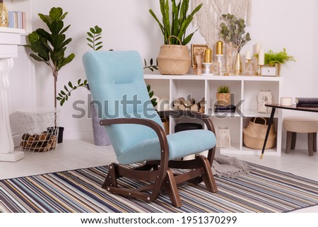 blue blue armchair shelves library books candles home furnishing comfort gold heat insulation indoor plants greenery vases Royalty-Free Stock Photo #1951370299