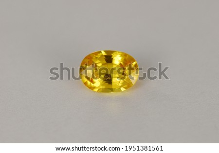 Natural yellow sapphire. Oval faceted clean setting gemstone. Precious gem for making gold jewelry. Color enhanced by beryllium heating. Light gray pattern background. Photo taken under day light.
