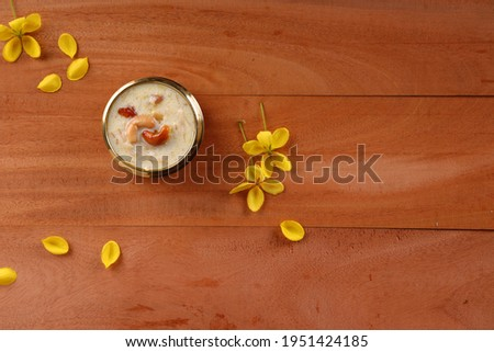 Vermecelli Payasam or Kheer ,South Indian main sweet dish made using vermicelli ,milk,sugar and dry nuts  and beautifully arranged in a brass vessel with golden shower flower in the wooden background.