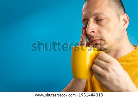 Image of sleepy man 40s in casual t-shirt drinking coffee while standing isolated over blue background. Morning portrait with cup of coffee. Sleepy guy holding a cup of coffee