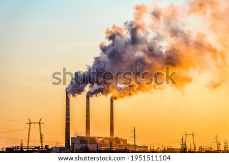 Sunset over the industrial city.Factory chimneys smoke.Environmental problem of environmental and atmospheric pollution.Climate change,environmental disaster.The sky is smoky with toxic substances Royalty-Free Stock Photo #1951511104