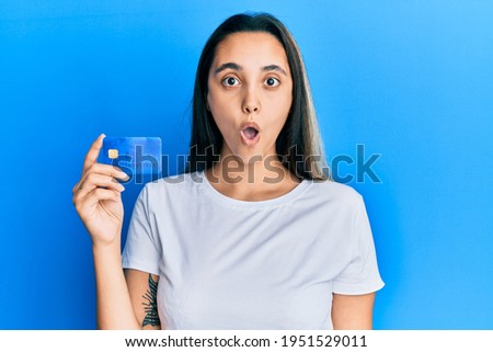 Young hispanic woman holding credit card scared and amazed with open mouth for surprise, disbelief face