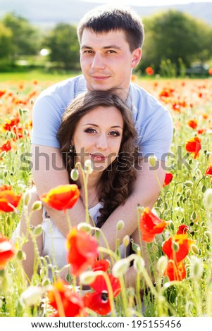 Lovely young happy couple reasting on a meadow full of poppies #195155456