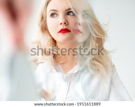 Beauty enhancement. Skin rejuvenation. Aesthetic cosmetology. Art portrait of pensive blonde woman with red lips makeup smooth face blur mirror reflection effect isolated on light.