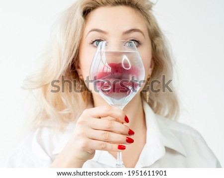 Beauty enhancement. Lip augmentation. Aesthetic cosmetology. Art portrait of blonde woman face with red lipstick makeup behind blur water glass prism magnifier isolated on white background.