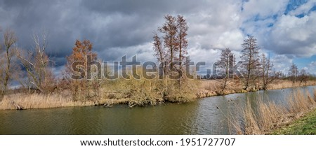 Early spring in the Spree Forest: thunderclouds over river Spree between the towns of Luebbenau and Luebben - panorama from 10 pictures