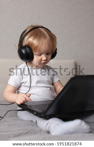baby todler baby blonde headphones home bed with a laptop on his feet watching a cartoon, listening music, playing games
