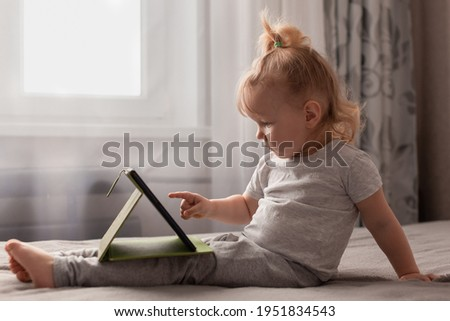 baby todler toddler sits bed home gray bedspread with touch panel tablet playing, watching cartoons, listening music