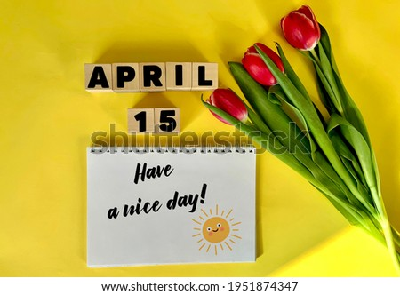 April 15 on wooden cubes on a yellow background.Next to a bouquet of tulips and a notebook with the inscription have a nice day .Calendar for April . Royalty-Free Stock Photo #1951874347