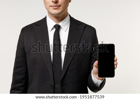 Close up cropped photo portrait shot young employee business corporate man in classic formal black suit tie work in office hold mobile phone blank screen workspace area isolated on white background