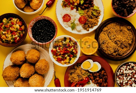 Typical Brazilian food seen from above on yellow background. Brazilian food. Royalty-Free Stock Photo #1951914769