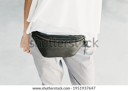 Black Leather Bum Bag Handfree Hip Pack Women Leather Bag. Model in gray pants, white blouse and black leather banana bag on a light gray background.