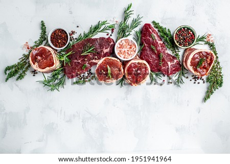Variety of raw beef meat steaks for grilling with seasoning on a light background. banner, menu recipe top view.