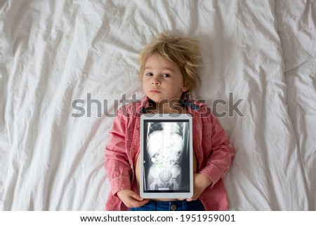 Toddler child, blond boy, holding x-ray picture on tablet of child body with swallowed magnet showing, child swallow dangerous object