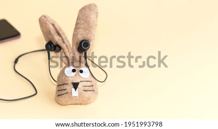 Toy funny bunny listening to music on smartphone through wired headphones.  Copy space beige background.