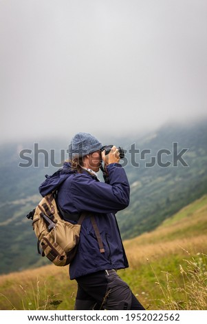 Traveler with camera is taking picture of landscape during hiking at mountains. Adventure in nature