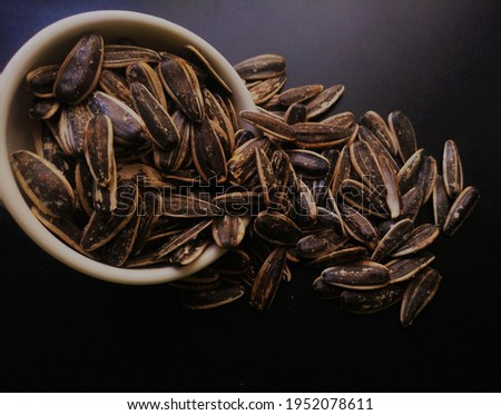 Sunflower Seeds on Black Wooden Background | Stock Photo High Resolution | Falling from bowl | Heap Of Seeds
