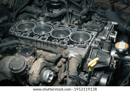 Short block with installed cylinder head gasket. Repair of a turbocharged diesel engine in a car workshop. Blur effect. Royalty-Free Stock Photo #1952119138