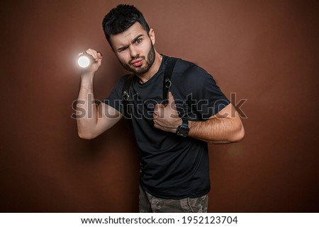 man with flashlight on brown background Royalty-Free Stock Photo #1952123704