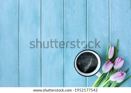 Steaming hot cup of coffee and pink spring tulip flowers over a rustic blue turquoise wooden table shot from top view.