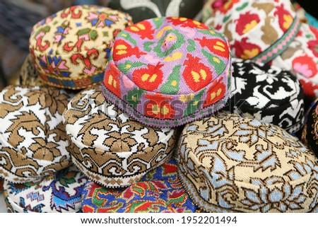 "Skullcap, ""tubereika"". A lot of knitted ethnic hats: skullcaps on counter of shop, store in Uzbekistan. Traditional national Uzbek headdress, costume, dress, handicraft. Uzbek fashion style. Tubeteyka Royalty-Free Stock Photo #1952201494"