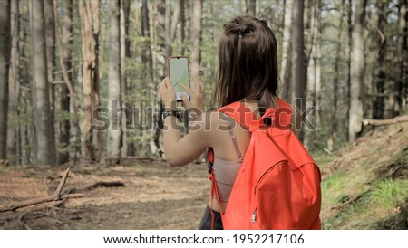 Woman standing in middle of forest, using navigation app on smartphone, following route with help of map, looking at device screen, using smartphone navigation while losing yourself in forest Royalty-Free Stock Photo #1952217106