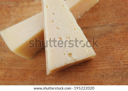 two fresh triangle french delicacy parmesan cheese pieces on wooden cut board over table #195222020