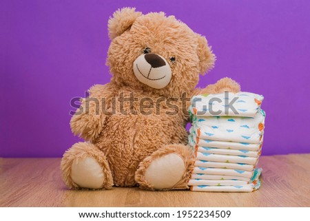 A teddy bear next to a stack of baby diapers. Baby toy teddy bear and diapers on the table against the background of a purple wall. Baby care, baby hygiene concept Royalty-Free Stock Photo #1952234509