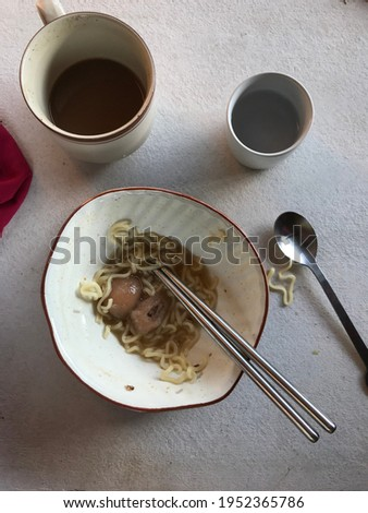 aftermath food, White bowl  with food scraps and an ground coffe explosions on a table, selective focus Royalty-Free Stock Photo #1952365786