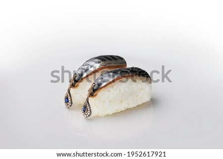Original japanese sushi with golden luxury earrings jewelry. Funny macro picture with selective focus and white background.