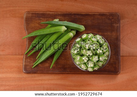 Okra or Lady's finger or Bhindi fresh green vegetable arranged  on a wooden board with a glass bowl full of okra sliced rings  with wooden background, selective focus ,top view.