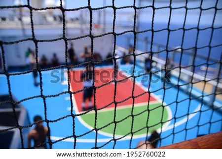 blurred picture of people playing basketball court on a cruise ship open deck