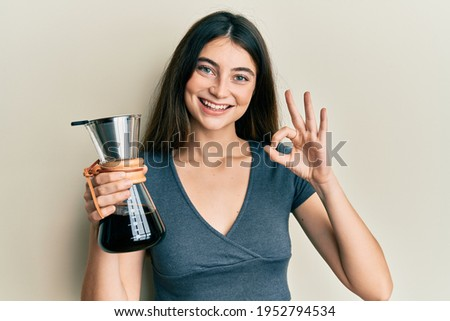 Young caucasian woman holding coffee maker with filter doing ok sign with fingers, smiling friendly gesturing excellent symbol